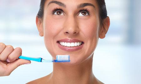 Mujer joven que sonríe con el fondo del cepillo de dientes de cuidado dental. Foto de archivo - 65721426