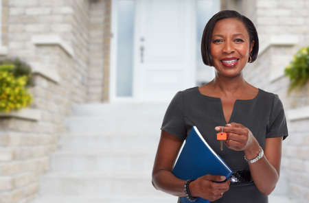Smiling afro american real estate agent woman with house key. Archivio Fotografico