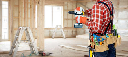 Builder handyman with construction tools on renovation background. Stock fotó