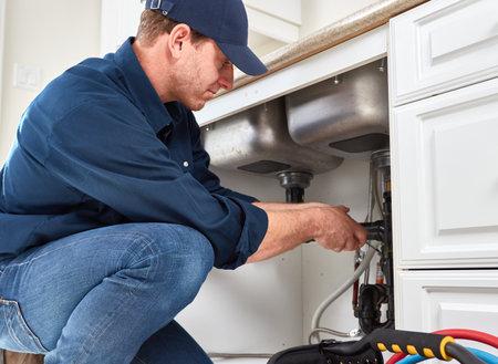 Plombier résidentiel faisant rénovation à la maison de la cuisine. Banque d'images - 66531034