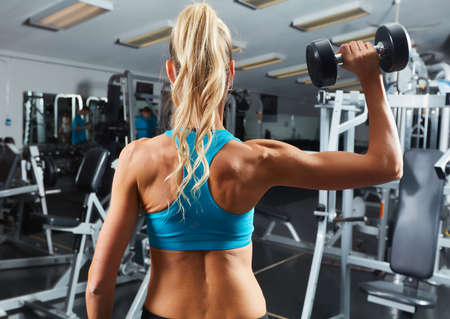 Strong young athletic girl exercising dumbbell workout Stock Photo