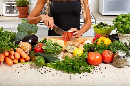 Handen van het meisje koken van groenten in de keuken. Stockfoto
