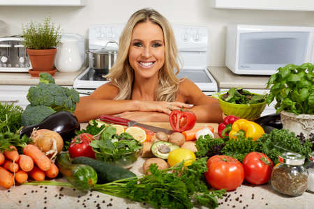 Young beautiful girl cooking vegetables in the kitchen.