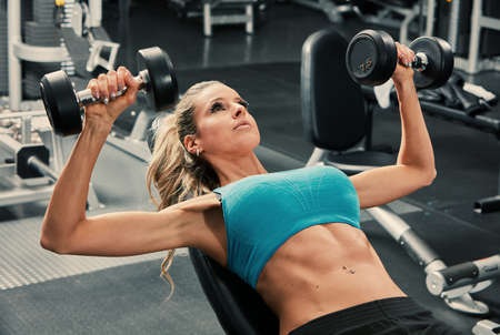 Strong young woman exercising with dumbbells in gym. Sport