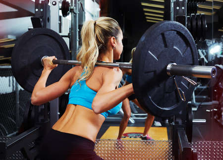 Strong young woman exercising squat with barbell in gym weightlifting. Sport