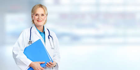 Beautiful medical doctor woman over blue clinic background. Stock Photo