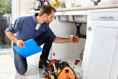 Professional plumber doing renovation in kitchen home. Stock Photo - 66163913