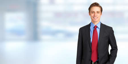 Young handsome caucasian business man over blue office, background Archivio Fotografico