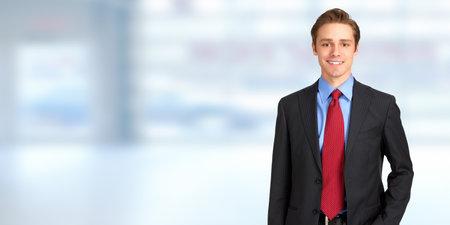 Jonge knappe blanke zakenman over blauwe kantoor, achtergrond Stockfoto