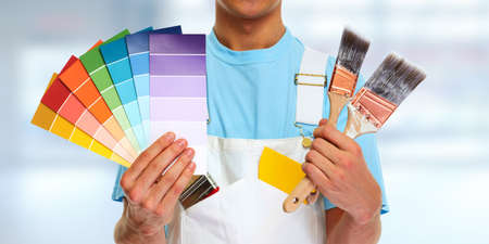 painter hands with painting brushes house renovation background.