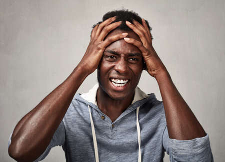 Depressed african american man having a headache over gray background