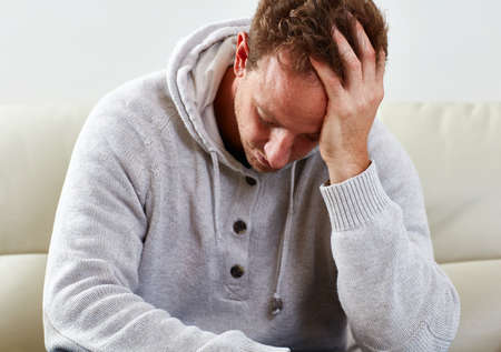 Depressed man having a headache in cozy apartment
