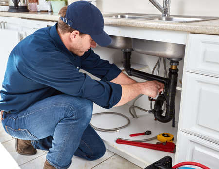 Residential plumber doing renovation in kitchen home.