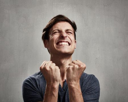 灰色の壁背景に幸せな興奮して若い男