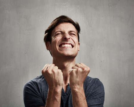 Happy excited young man over gray wall background Stock Photo - 66944864