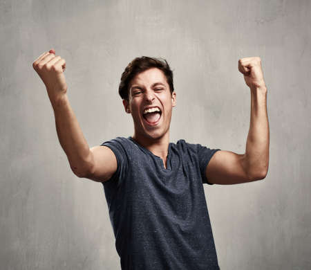 Happy excited young man over gray wall background