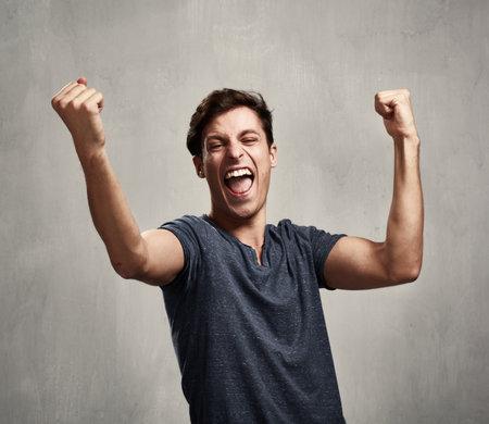 Glücklich aufgeregten jungen Mann über grauen Wand Hintergrund Standard-Bild - 66944875