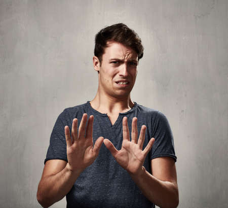 Il giovane disgusto espressioni del viso ritratto su sfondo grigio.