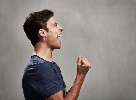 Happy excited young man over gray wall background Stock Photo - 66944833