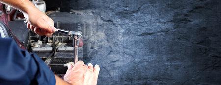 Handen van automonteur met moersleutel over donkere muur achtergrond. Stockfoto