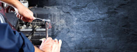 Hands of car mechanic with wrench over dark wall background. Archivio Fotografico