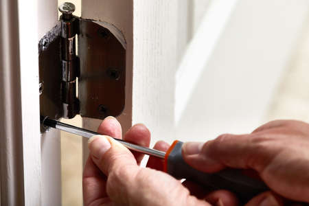 Hands with screwdriver fixing a door hinge. Stock Photo