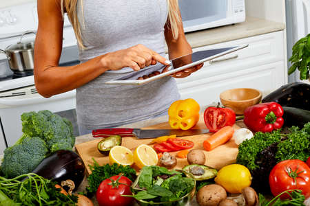 Hands of woman with tablet in the kitchen. Stock Photo