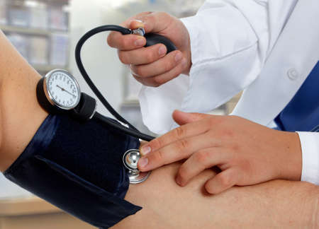 Doctor measuring blood pressure with sphygmomanometer