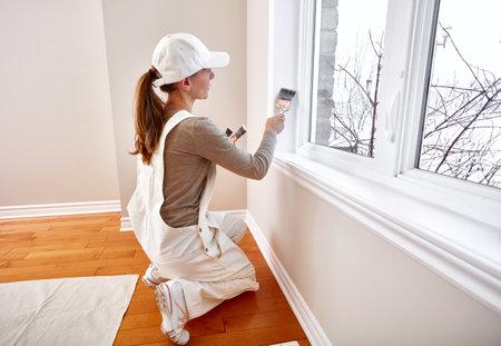 Woman painting window trim Stockfoto