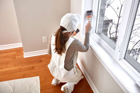 Woman painting window trim Imagens