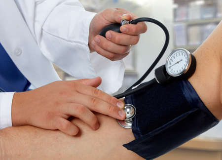 Doctor measuring blood pressure with sphygmomanometer