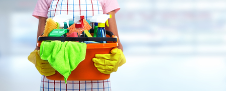 Hands of cleaner woman with cleaning products on blue background.