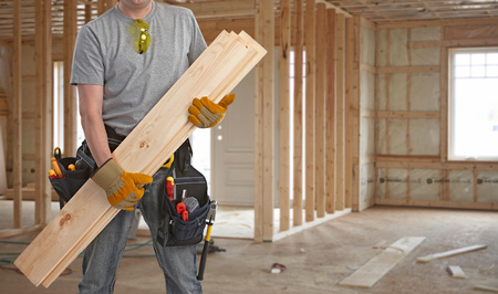 Builder handyman with wooden planks. Imagens