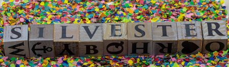New Years Eve written on wooden blocks in German language isolated on confetti background