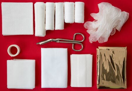 Insides of a first aid kit isolated on a red background