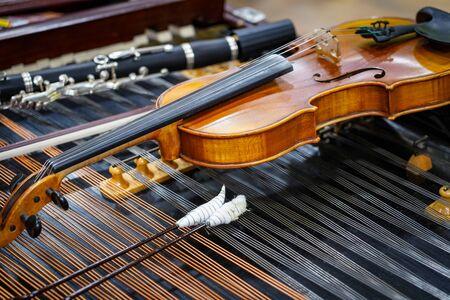 Antique violin and violin bow lying on dulcimer.