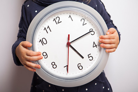 Child holding clock which shows after five. Time to come back home.