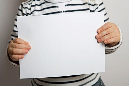 blank sheet: Hoja en blanco de papel en las manos del ni�o