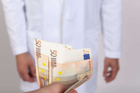 doctor money: Close-up doctor takes money