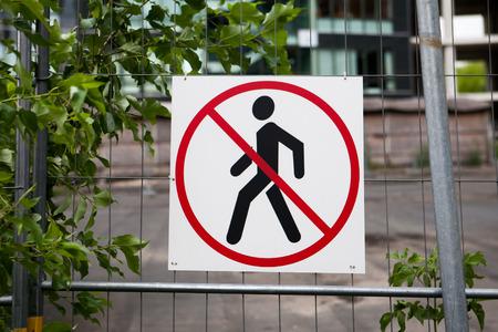 no pase: No hay se�ales de entrada en la cerca en sitio de construcci�n con casa en construcci�n y los �rboles verdes en el fondo Foto de archivo