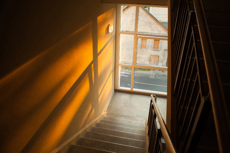 backstairs: Staircase of apartment building with sunset light playing on the wall