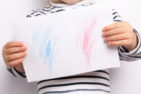 white sheet: A small child holding a white sheet of paper with painted French flag