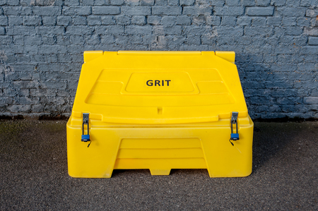 grit: Yellow Plastic Box With Grit Salt Ready For Winter