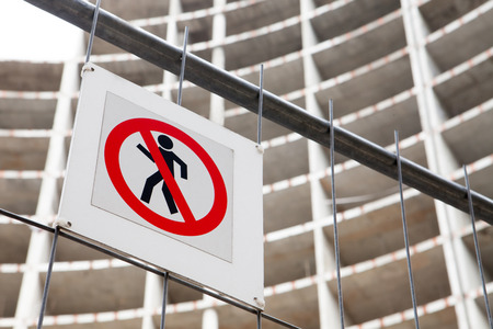 No entry sign on the fence in contruction site with house under construction. Stock Photo