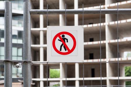 no pass: Ninguna señal de entrada en la cerca en el sitio de construcción con casa en construcción.