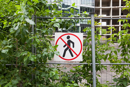 no pase: Ninguna señal de entrada en la valla en sitio de construcción con casa en construcción y árboles verdes en el fondo