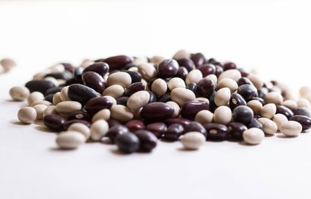 Multi-colored beans on a white background. Red and white beans in a background. Assortment of dried multi-colored beans, healthy ingredient. Bright multi-colored beans. A complete source of protein.