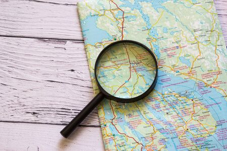 Magnifying glass and ancient map on the wooden background