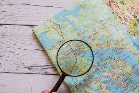 Magnifying glass and ancient map. Copyspace for text. Top view. Flatlay on wooden background.