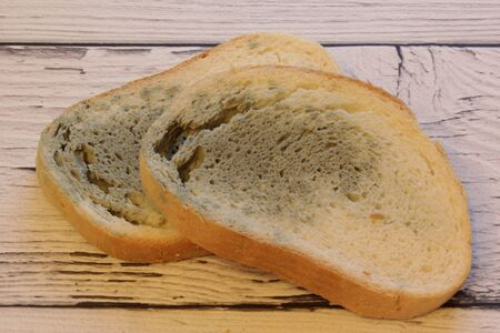 Mold growing rapidly on moldy bread on wooden background. Mildew on a slice of bread. Stale bread, covered with mildew.